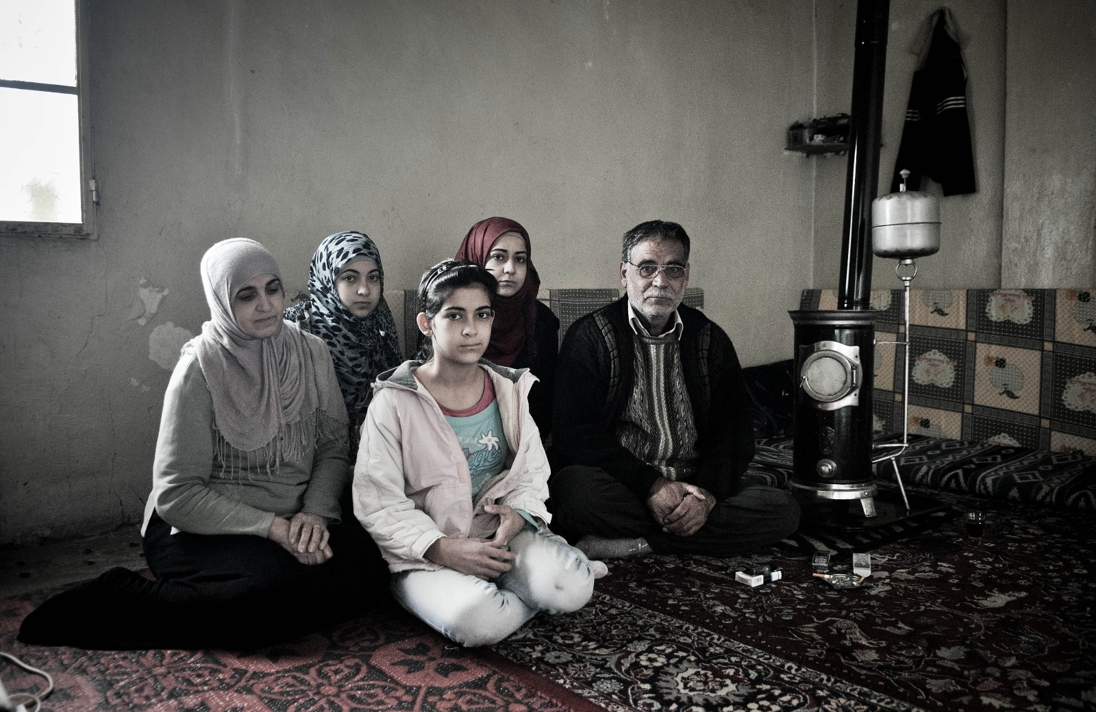 """Aarsal - La famiglia di Najad. Najad ha 24 anni e viene da Homs, una delle città più martoriate dalla guerra siriana. Quando il padre ha preso la decisione di lasciare la città, e di recarsi ad Arsaal per sfuggire alla guerra, le ha raccomandato di non prendere troppa roba con sé, """" Si tratterà di un mese o due, ritorneremo presto a casa"""". Questo succedeva nel gennaio del 2012, e dopo un anno la famiglia di Najad si trova ancora in Libano, nella stessa casetta fatta di due stanze e un bagnetto fuori dal cortile."""