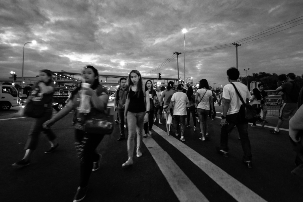 Girls crossing the road in Angeles City. The city is known as a main source of entertainment in the Philippines. Prices for women in go-go bars vary depending on the venue.